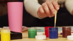 Jars with colored gouache stand on the table in the background drawing girls Stock Footage