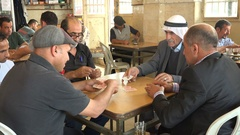 Daily life in the West Bank, men play cards and drink coffee tea Stock Footage