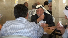 Senior Palestinians play cards in a traditional tea house in Ramallah Stock Footage
