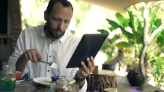 Young man reading news on tablet computer during meal in cafe Stock Footage