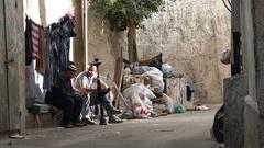 Young Palestinian men smoke from imitation rifle in narrow streets Ramallah Stock Footage