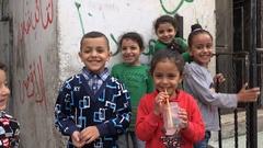 Palestinian kids smile at camera in Ramallah permanent refugee camp Stock Footage