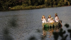 Three beautiful girls in the Slavic clothes in a boat on the river. women pass Stock Footage