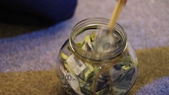 Child gets bank notes from a glass jar with chopsticks Stock Footage