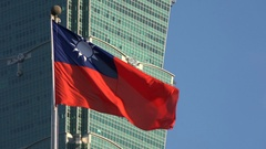 The Taiwanese national flag in front of the iconic Taipei 101 building Stock Footage