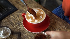 Close up of female hands adding brown sugar into coffee in cafe, slow motion Stock Footage