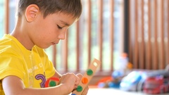 Child playing in the game room, wooden designer. Beautiful boy. Stock Footage