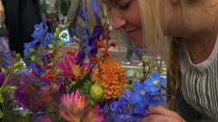 Young Woman Enjoys Smelling Flowers At Open Air Market In Amsterdam, Netherlands Stock Footage