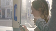 Mixed Race Young Woman Uses Phone, While Friend Braids Hair, On Light Rail Train Stock Footage