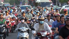 Motorbike riders wear mouthpieces, heavy traffic and smog Vietnam (HCMC) Stock Footage