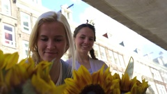 Young Woman Smells Sunflower Bouquets, Her Friend Points To Something Stock Footage