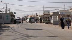 Syrian refugees walk and cycle through main street Zaatari camp in Jordan Stock Footage