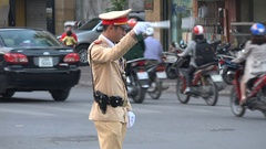Vietnamese police officer guides traffic in central Hanoi during rush hour Stock Footage