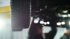Car service - mechanic unscrewing automobile device while working under a lifted Stock Footage