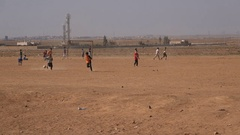 Syrian refugees play football (soccer) on a dry pitch in Zaatari camp in Jordan Stock Footage