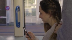 Friends Ride The Light Rail, Reads Something Funny On Phone, Friend Braids Hair Stock Footage