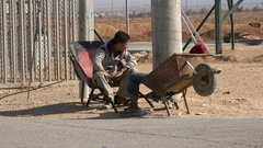 Syrian boys play with wheelbarrows in refugee camp Jordan, Middle East region Stock Footage