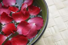 Red petals floating in bowl Stock Photos