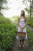 Blonde woman standing on pathway holding basket Stock Photos