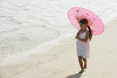 Little girl walking on beach under pink umbrella Stock Photos
