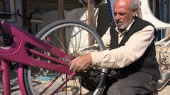 Displaced Syrian refugee at work in makeshift bicycle shop Zaatari camp Stock Footage