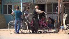 Syrian refugees bicycle repair shop in Zaatari camp in Jordan Stock Footage