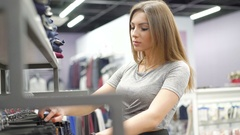 Stylish girl looking on clothes in fashionable boutique. 4K Stock Footage