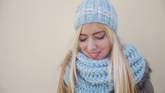 Young woman dressed in light blue winter hat and scarf against a wall smiling to Stock Footage
