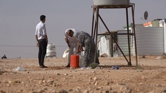 Displaced Syrian family fills water in refugee camp Middle East Stock Footage
