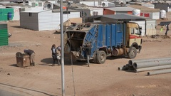Garbage truck, trash disposal in Syrian refugee camp Jordan Stock Footage