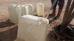 Syrian refugees fill jerrycans with water in Zaatari camp Jordan Stock Footage