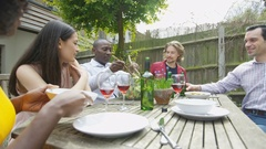 4K Happy friends enjoying lunch & drinks in the garden on a summer day Stock Footage