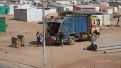 Garbage disposal truck in Syrian refugee camp Middle East Stock Footage
