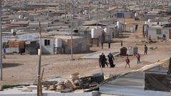 Syrian refugees walk past makeshift homes in the Zaatari camp in Jordan Stock Footage