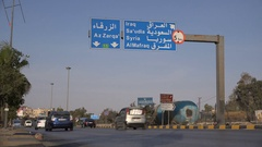 Jordanian traffic drives past exit to highway with Syria, Iraq, and Saudi Arabia Stock Footage