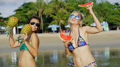 Two beautiful sexy daring lesbians, sunglasses keep tropical fruit on the beach Stock Footage