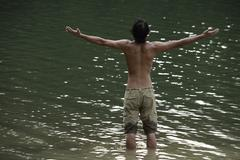 Young man standing in lake, arms open wide Stock Photos