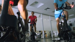 The trainer and young sportsmen are training on the exercise bikes in the gym Stock Footage