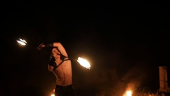 Fire show performance. Three handsome male fire performers dance twirling two Stock Footage