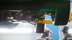 Car lifted in automobile service for fixing, water flows from the wheel Stock Footage