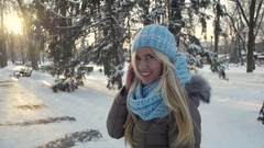 Young gorgeous lady in a warm hat and scarf walking in the winter park Stock Footage
