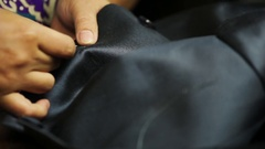 Sewing a button onto a bespoke tailored suit Stock Footage