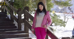 Woman in pink snowsuit relaxing on stairs Stock Footage