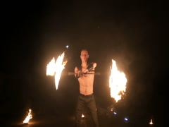 Fire show. Handsome male fire performer twirling fire baton with several wicks Stock Footage