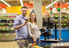 Couple buying food at grocery at cash register Kuvituskuvat
