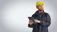 Mid Shot of a Worker in a  Hard Hat Holding Tablet Computer and Looking Around.  Stock Footage