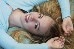 Head shot of young blonde woman laying down smiling Stock Photos