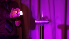 LED lamp lights up in the hands of an electric spark Stock Footage