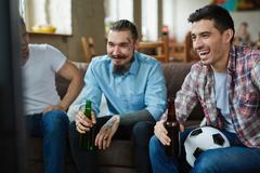 Friendly guys with beer watching football match on TV Stock Photos