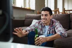 Guy with anxious expression sitting in front of tv set during football match Stock Photos